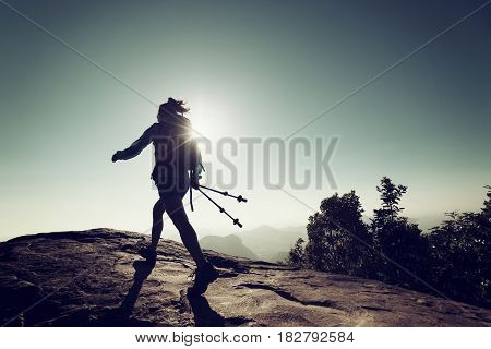 successful woman backpacker hiking on sunrise mountain top