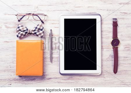 Men's accessories and tablet on white wooden surface