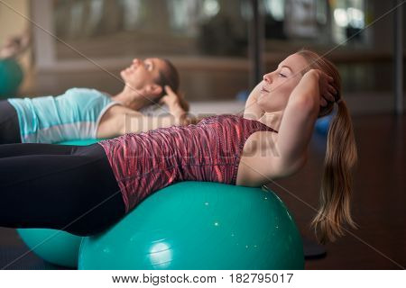 Two Women Exercising With Balls In Gym
