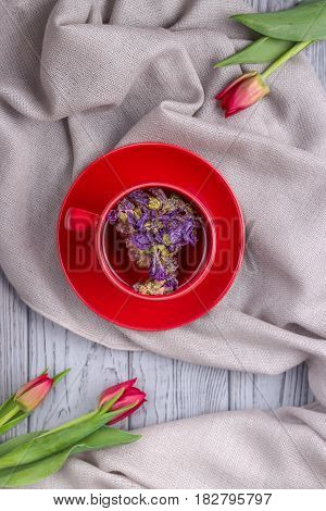 Herbal tea with mallow flowers and red tulips on a gray background. Top view