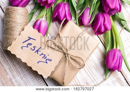 Polish words I MISS YOU and bouquet of tulips on wooden background
