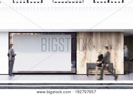Business people are passing by a shop window with a large horizontal poster a bench and a white balcony on the second floor. Concept of promotion. 3d rendering mock up