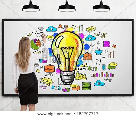 Rear view of a businesswoman drawing a bright idea sketch on a whiteboard in a room with three ceiling lamps.