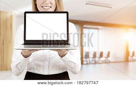 Close up of a blond businesswoman holding a laptop with a blank screen and standing against an office background. Mock up toned image