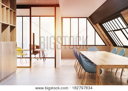 Attic conference room interior with a long wooden talbe surrounded by blue chairs and a bookcase on the left. 3d rendering toned image.
