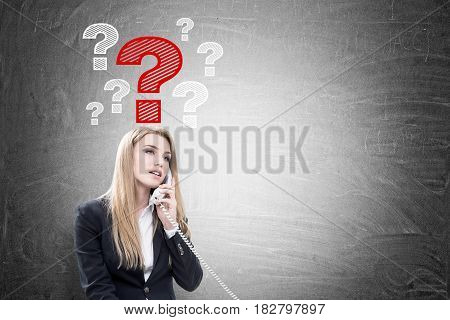 Portrait of a blond businesswoman talking on the phone while sitting near a blackboard with question marks drawn on it. Mock up