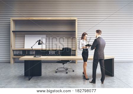 Man and woman in an interior of a clerk office with a white perforated wall a large desk and a bookcase with folders and a small poster. 3d rendering mock up