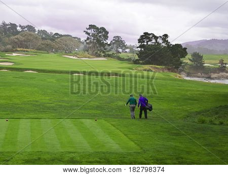 Golfer and caddie walk down fairway after teeing off