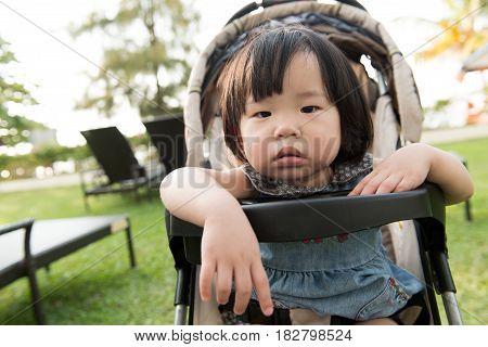Little Asian toddler in sitting stroller at the resort beach