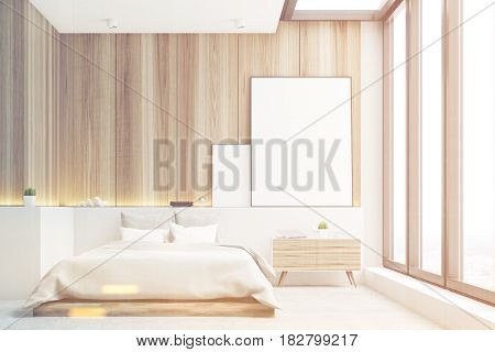 Front view of a bedroom with light wooden walls a double bed and two blank posters to the right of it. 3d rendering mock up toned image