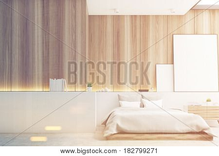 Front view of a bedroom with light wooden walls a double bed and two blank posters to the right of it. Large wall fragment to the left. 3d rendering mock up toned image