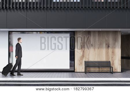 Businessman witha suicase is passing by a shop window with a large horizontal poster a bench and a white balcony on the second floor. Concept of promotion. 3d rendering mock up