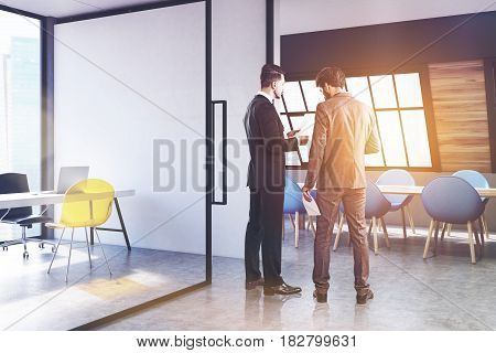 Poeple are standing in a corner of an attic conference room interior with a long wooden talbe surrounded by blue chairs and a CEO office on the left. 3d rendering toned image.