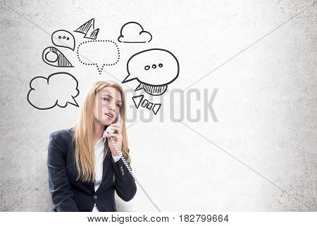 Portrait of a blond businesswoman talking on the phone while sitting near a concrete wall with speech bubbles drawn on it
