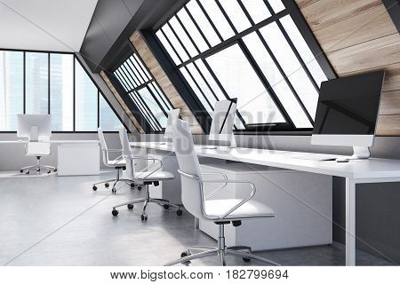 Attic office interior with rows of computer tables standing along the walls and windows in the roof. 3d rendering.