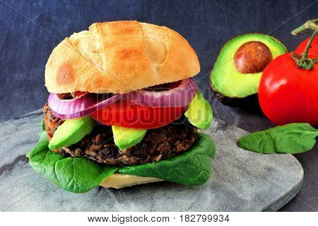 Veggie Bean And Sweet Potato Burger With Avocado And Spinach Against A Dark Background