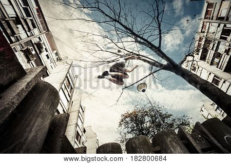 young man doing parkour jump  in  the city  sunny spring summer day