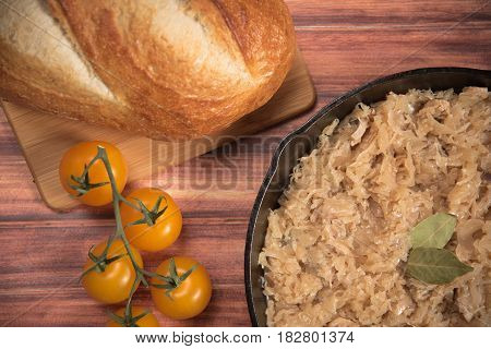 homemade braised sauerkraut in a frying pan on a wooden background