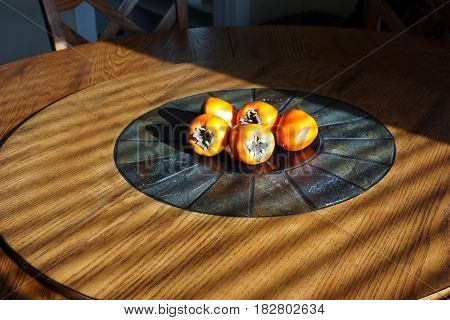 Five ripe persimmons sit in the center of a lazy susan dining table.