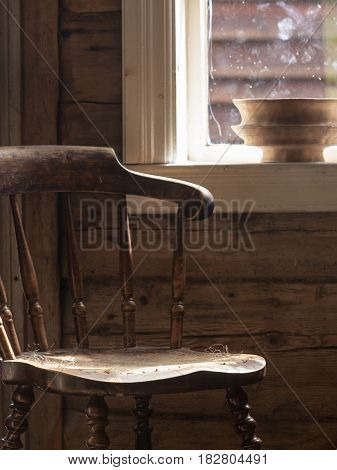 Oldfashioned design in architecture concept. Vintage wooden chair in old cottage next to window.
