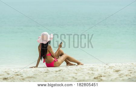 Beach vacation girl listening to music in headphones on a mobile phone during summer travel holiday. Woman relaxing sunbathing on sand sitting wearing sun hat.