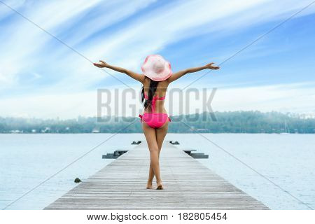 Freedom woman in free happiness bliss on beach. happy multicultural female model in bikini enjoying serene ocean nature during travel holidays vacation outdoors.
