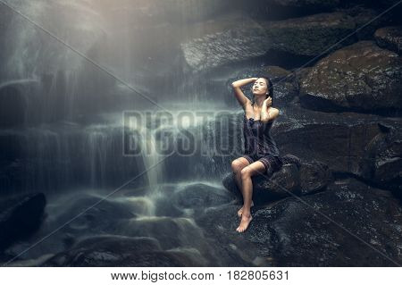 Beautiful Asian woman in waterfall, countryside of Thailand