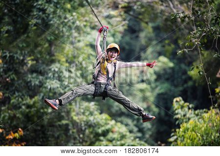 Woman Tourist Wearing Casual Clothing On Zip Line Or Canopy Experience In Laos Rainforest Asia