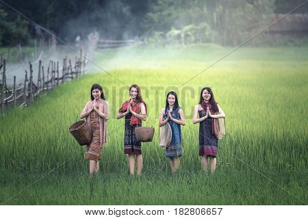 Thai women welcome sawasdee at rice field countryside of Thailand