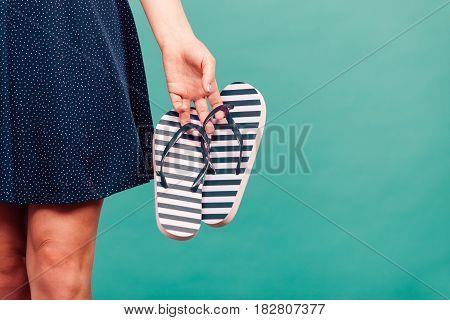 Woman Wearing Short Navy Dress Holding Flip Flops