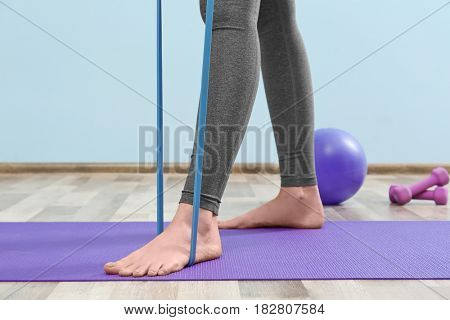 Girl training with elastic in gym