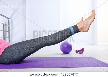 Female legs training with elastic in gym