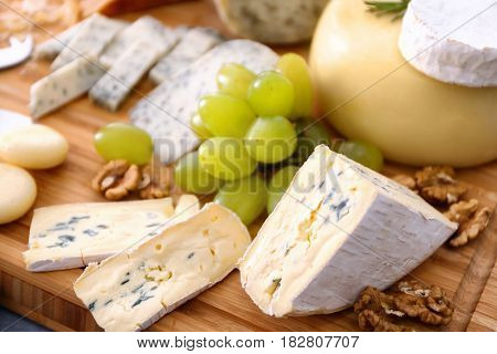 Sliced cheese with grape and nuts on wooden board
