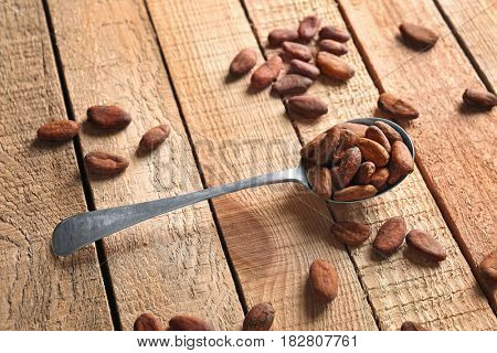 Spoon with aromatic cocoa beans on wooden table