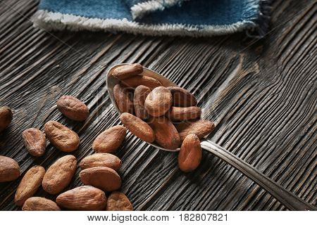 Spoon with aromatic cocoa beans on wooden background