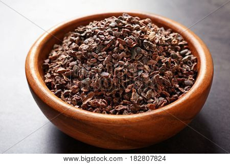 Bowl with aromatic cocoa nibs on gray table