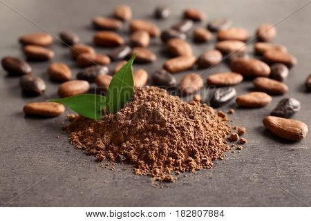 Aromatic cocoa powder and beans on wooden table