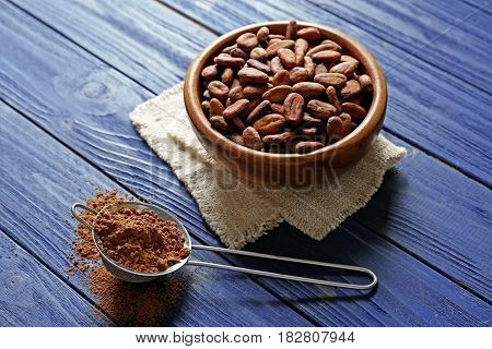 Cocoa beans in bowl and sieve with powder on wooden table