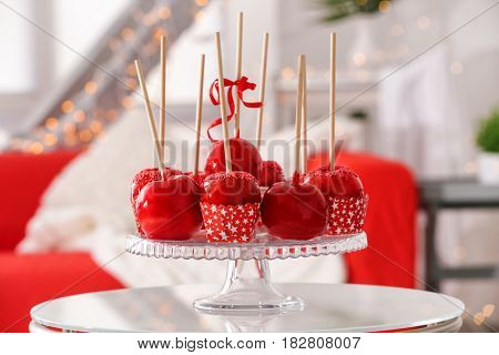 Composition of delicious toffee apples on glass stand against blurred background