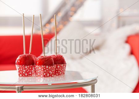 Delicious holiday apples in carton boxes on glass table against blurred background