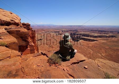 A male hiker sits at the edge of a cliff in Utah's Canyonlands National Park.
