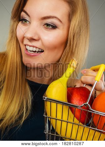 Buying healthy food vegetarian gluten free vegan products. Happy woman holding shopping cart with fruits inside