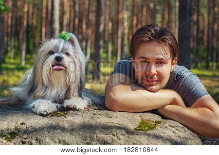Young man with shih tzu dog portrait in forest