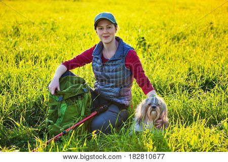 Young woman tourist resting with shih tzu dog after travel at field with sunset light