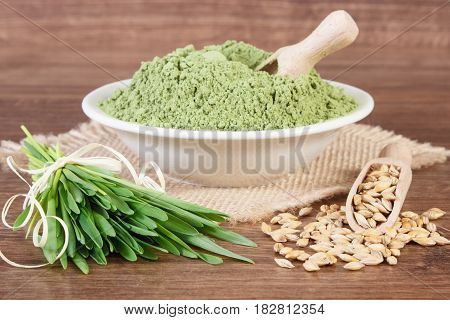 Heap Of Young Powder Barley, Barley Grass And Grain On Jute Canvas, Wooden Background