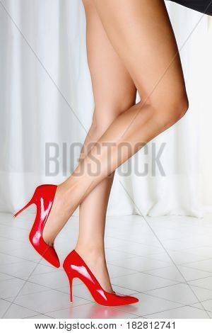 Long sexy legs of a caucasian woman wearing red shoes
