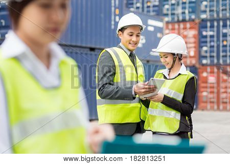Asian businessman and Asian secretary working with container Cargo freight ship in shipyard for Logistic Import Export background