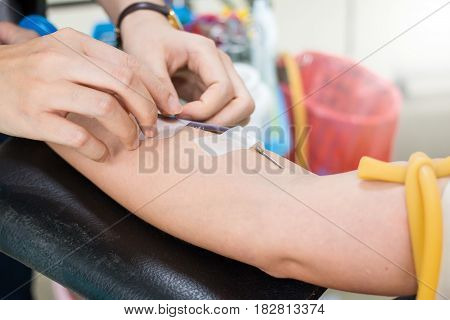 Donate blood using a needle in the arm.