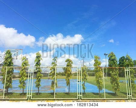 Beatiful blue sky on the basketball sport field with tree fence background in summer in thailand
