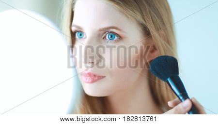Pretty woman applying make up with brush.